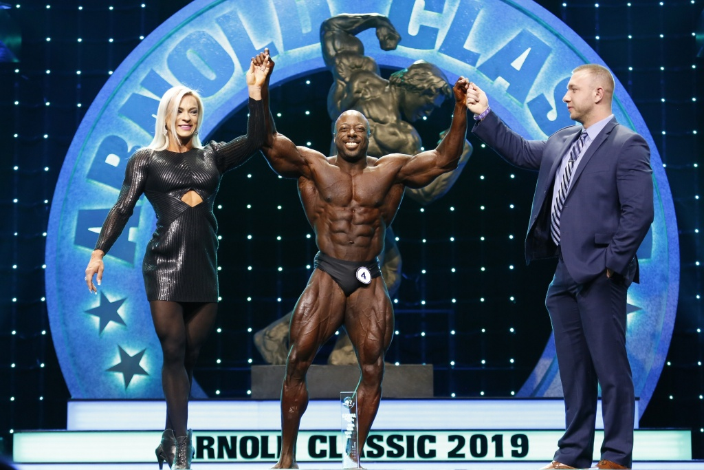 2019 Arnold Classic Men's Physique winner George Peterson congratulated by Carol Zawadzki from Midway Labs USA and Joseph Pircher from Animal Photo by Dave Emery(2).jpg